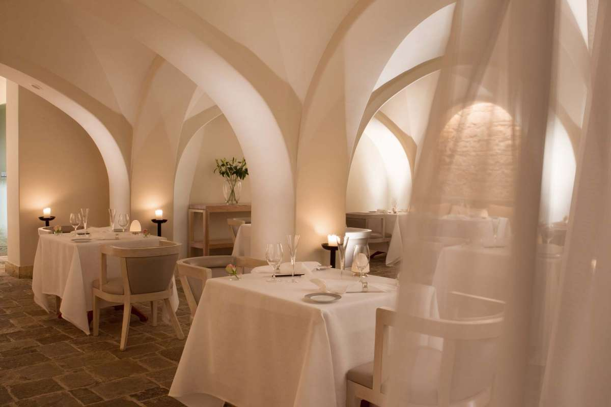 Looking sideways on two laid tables at Basiliko Restaurant at Anassa Hotel