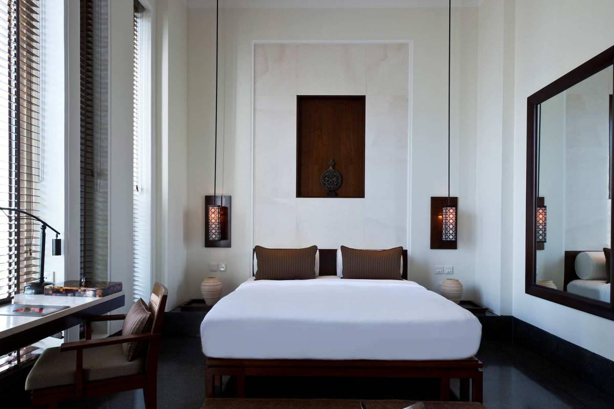 View on the bed, a small desk and a big wall mirror at the Chedi Muscat