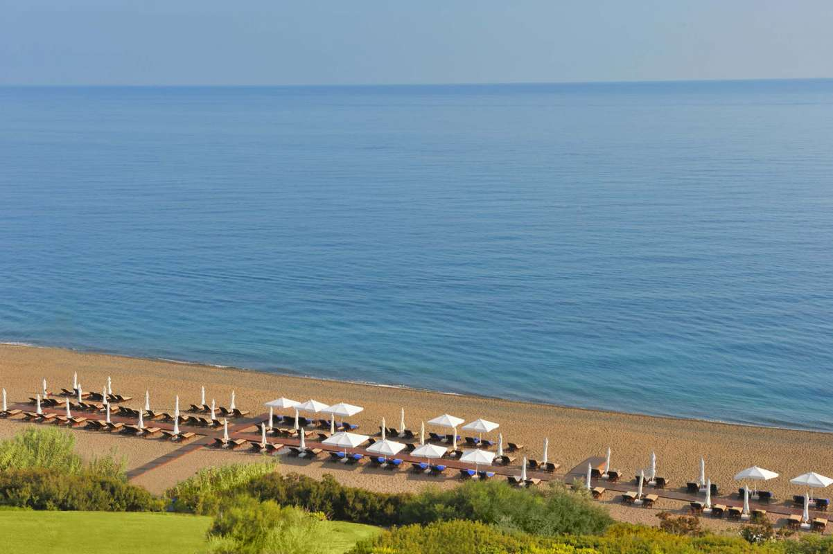 View on the beach and the parasols at Anassa Hotel's beach
