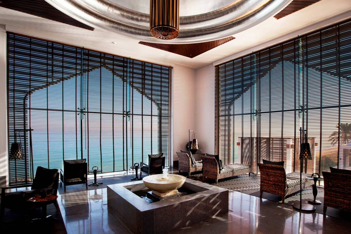 View into the Relax Room of the spa at chedi muscat, with a little water fountain in the middle of the room, relax chairs and big, ground-lever windows which open the view towards the sea